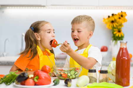 Brother feeds his sister with vegetables in the kitchen. Stockfoto