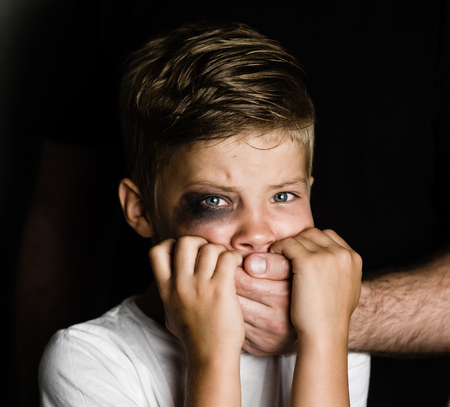 Scared young boy with an adult mans hand covering his mouth. Looking at camera. Stock Photo