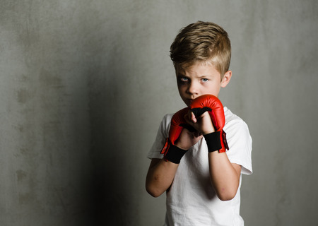 Beaten young boy with red boxing gloves.Space for text.