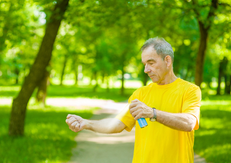 Senior man  spraying insect repellents on skin.