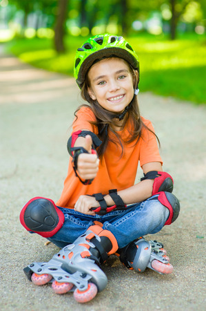 Happy girl in a protective helmet and protective pads for roller skating sitting on the road and showing thumbs up.