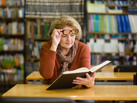 An elderly woman with glasses reads a book.