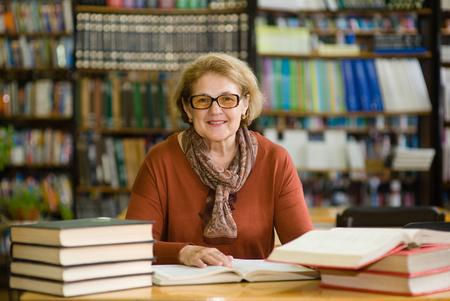 Heureuse femme âgée avec des livres dans la bibliothèque. Banque d'images - 84271986