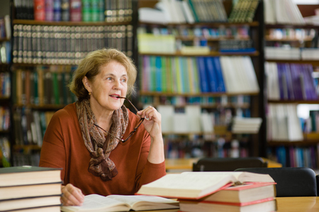 Thoughtful elderly woman in library. Stock Photo