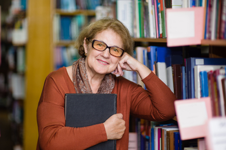 Smiling elderly woman with book in library.