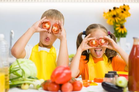 Happy kids having fun with food vegetables at kitchen holds tomatoes before his eyes like in glasses.