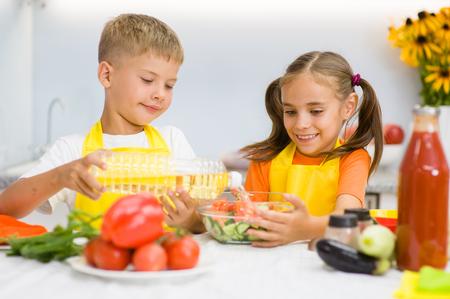 niños desayunando: Los niños felices vierten el aceite de girasol en una ensalada en la cocina.