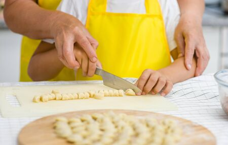 teaches: Close up mother teaches her son how to cook food in the kitchen.