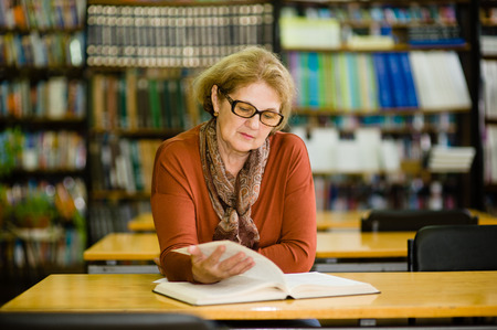 Senior woman reading book in library. Stock Photo