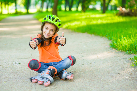 Happy girl in a protective helmet and protective pads for roller skating sitting on the road and showing thumbs up. Space for text.