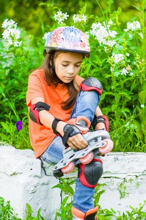 oneself: Girl puts on roller skates.