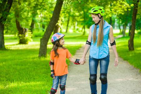 Madre e hija se divierten en la naturaleza, patinar.