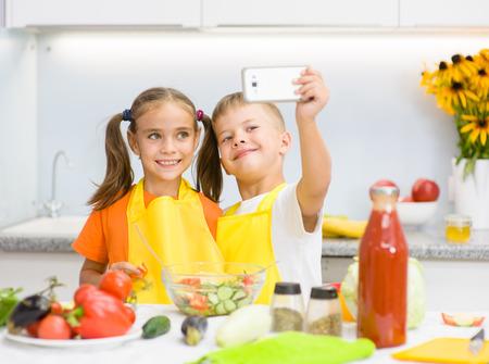 niños desayunando: Los niños felices hacen selfie en la cocina. Foto de archivo