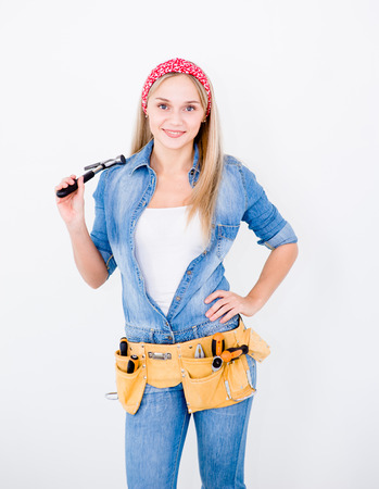 Independent woman with toolbelt and hammer on white background.