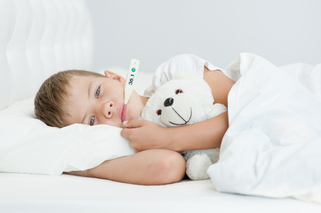 Sick boy with thermometer in mouth lying in bed and hugging a toy bear. Stock Photo