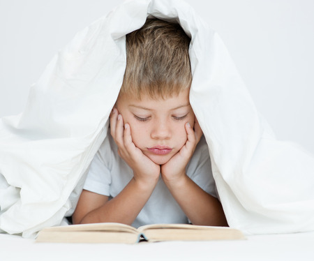 bedtime story: The boy is reading a book under the blanket. Stock Photo