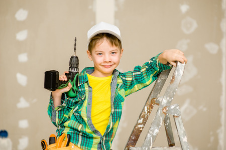 Portrait of a happy child on a ladder with tools and toolbelt. Stock Photo
