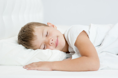 Little boy sleeping in bed.