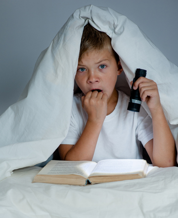 Frightened boy is reading a book under a blanket.