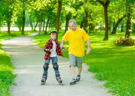 teaches: Father teaches his son to ride roller skates.