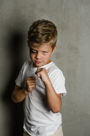 Beaten young boy is ready to fight.
