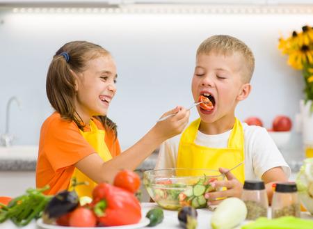 niños desayunando: Hermana alimenta a su hermano con verduras en la cocina.