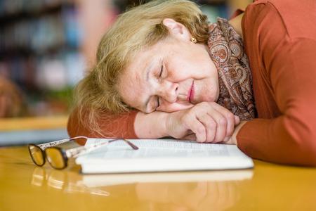 An elderly woman is sleeping in a library.