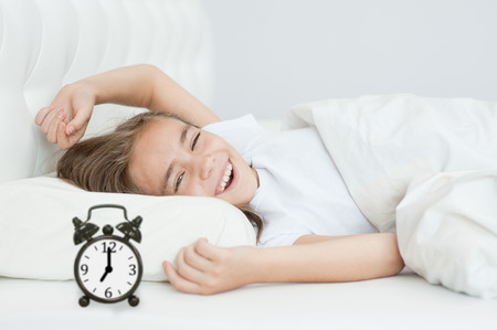 waking up the girl stretches out in bed early in the morning. Stockfoto
