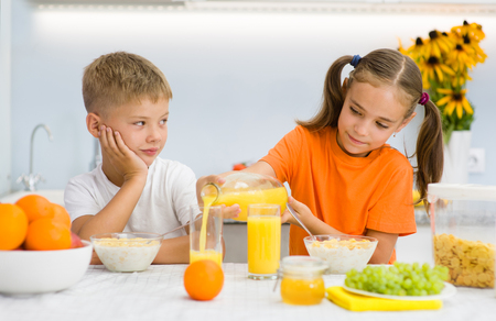 girl pours orange juice to her brother.