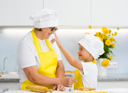 boy trying to smear nose with flour his grandmother in kitchen.