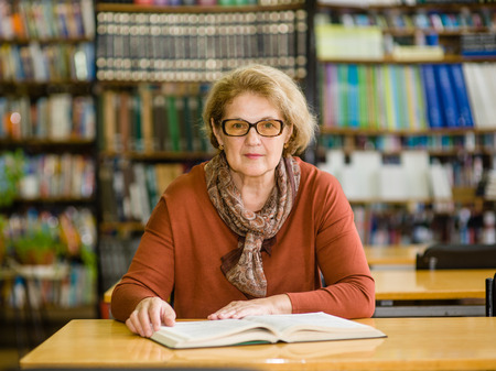 Portrait of an elderly woman with a book in the library.