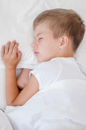 tired: Little boy sleeping in bed. Top view. Stock Photo