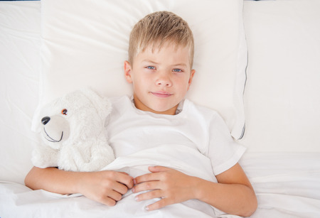 tired: Little boy lying in bed with toy bear. Top view.