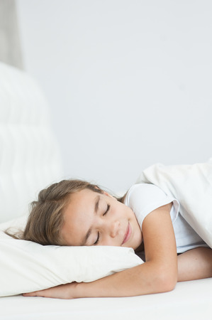 tired: Beautiful little girl sleeping in bed. Space for text. Stock Photo