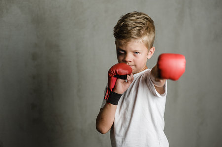 Beaten young boy punching with red boxing gloves. Space for text.
