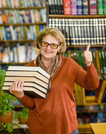 Happy senior woman with books in library showing thumbs up. Stock Photo