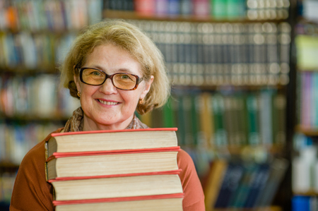 Smiling elderly woman with books in library. Space for text.