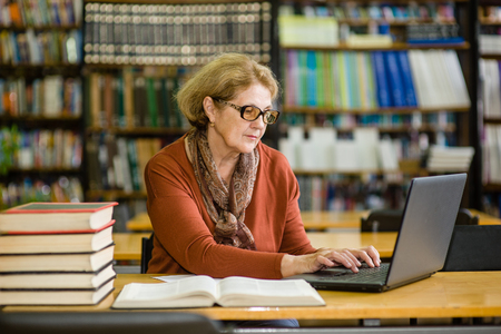 Senior woman using laptop in library. Stock Photo
