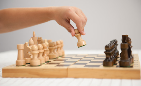 the child plays chess and makes the first move a pawn.