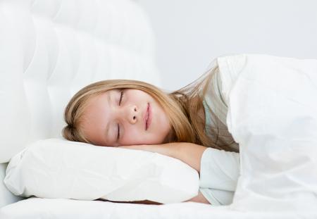 tired: Happy teen girl sleeping in bed.