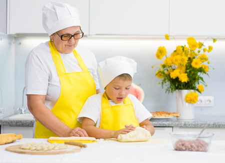 teaches: Happy grandmother teaches the child to knead the dough in the kitchen. Stock Photo