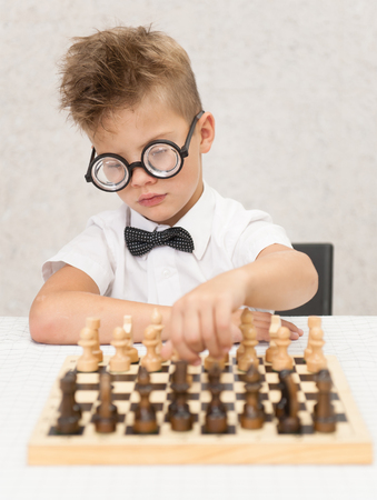 Smart boy plays chess and makes the first move a pawn. Stock Photo
