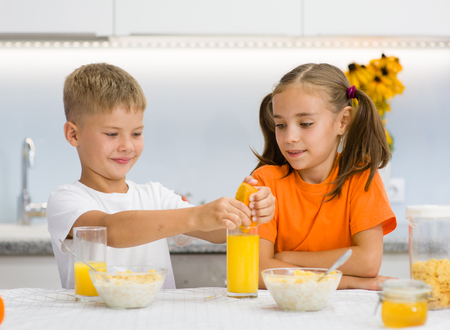 Brother squeezes orange juice for breakfast his sister.