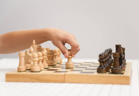 school strategy: little boy plays chess and makes the first move a pawn.