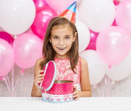 Happy girl opens birthday present. Stock Photo