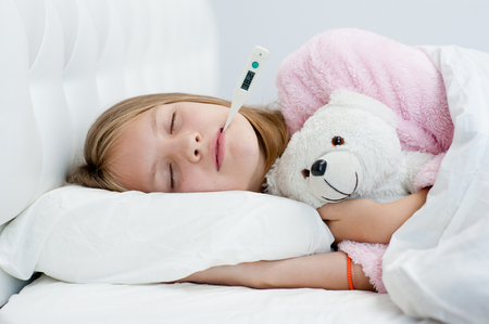 sick girl with toy bear lying in bed with a thermometer in mouth. Stock Photo