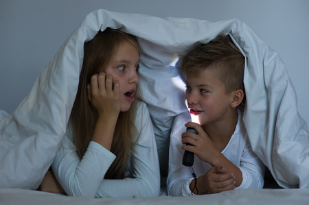 children tell each other terrible stories for the night under the blanket. Stock Photo