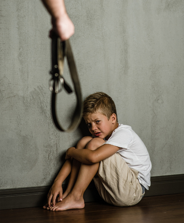 Domestic violence: Mans hands with belt and frightened beaten son.