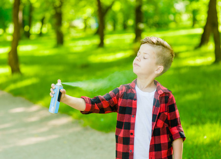 Boy spraying insect repellents on skin . Banco de Imagens
