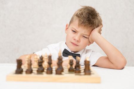 Pensive little boy plays chess.